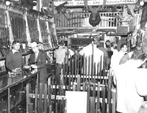 Hy Hunter behind the counter of his shop, examining Great Western single actions with the legendary Carbine Williams.
